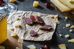 Slices of dried meat, chopped Spanish hard cheese manchego on wooden cut, sliced Italian pecorino toscano, red grapes Royalty Free Stock Photo