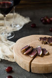 Slices of dried meat on wooden cut, red grapes and two glasses of red wine Stock Image