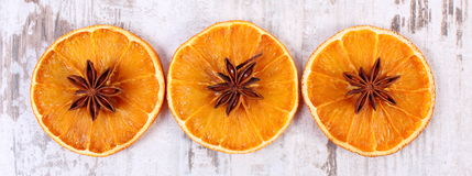 Slices of dried orange and star anise on old wooden background Royalty Free Stock Image