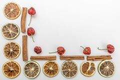 slices of dried oranges, dried strawberry and cinnamon on a white background royalty free stock image