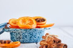 Slices of dried oranges or tangerines with anise and cinnamon in a blue bowl on a light background. Vegetarianism and healthy