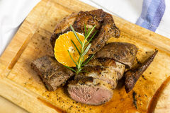Slices of duck breast with rosemary and slice of orange on board Royalty Free Stock Photo