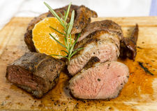 Slices of duck breast with rosemary and slice of orange on board Stock Photo