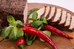 Slices of fillet of pork with chili and lettuce around. Cut pork into slices on a cutting board with chillies and salad around Royalty Free Stock Image