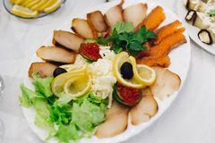 Slices of fish and black olives on a plate with lemon Royalty Free Stock Image