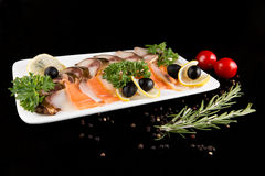 Slices fish, decorated by lemon and olives Stock Photo