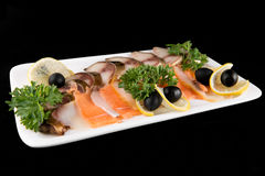 Slices fish, decorated by lemon and olives Royalty Free Stock Photo