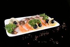 Slices fish, decorated by lemon and olives Royalty Free Stock Photos