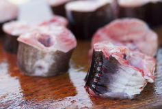 Slices of fresh fish on market. Slices of bloody red fresh fish on wooden surface at market Royalty Free Stock Images