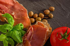 Slices of fresh homemade Alpine Baguette with jamon, basil, olives and tomato on black. stock image