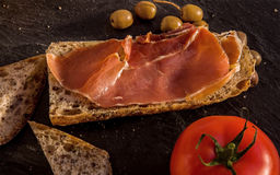 Slices of fresh homemade Alpine Baguette with jamon, olives and royalty free stock images