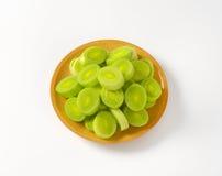 Slices of fresh leek. Bowl of fresh leek slices on white background Royalty Free Stock Photography