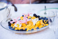 Slices of fresh mango and flowers on glass plate. Slices of fresh mango, blueberries and flowers on glass plate at the wedding table stock photos