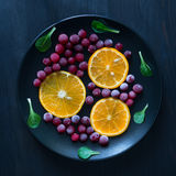 Slices of fresh orange and frozen cranberries on the dark backgr Royalty Free Stock Photo