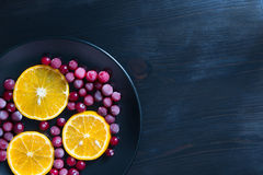 Slices of fresh orange and frozen cranberries on the dark backgr Stock Photo