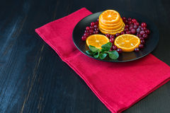 Slices of fresh orange and frozen cranberries on the dark backgr Royalty Free Stock Photography
