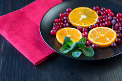Slices of fresh orange and frozen cranberries on the dark backgr Royalty Free Stock Photos
