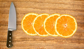 Slices of fresh orange and knife on cutting board Royalty Free Stock Photography