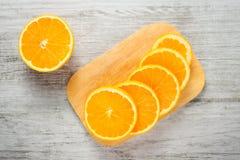 Slices of fresh oranges on white wood background Royalty Free Stock Image