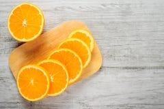 Slices of fresh oranges on white wood background Royalty Free Stock Photo