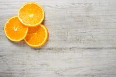 Slices of fresh oranges on white wood background Stock Photography