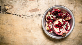 Slices of fresh pomegranate in a bowl. On wooden table. Royalty Free Stock Photos