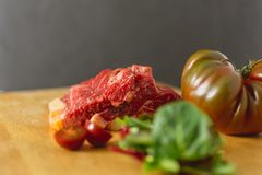 Slices of fresh raw beef steak on wooden board on black background with salad and tomatoes royalty free stock photo