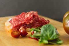 Slices of fresh raw beef steak on wooden board on black background with salad and tomatoes royalty free stock images