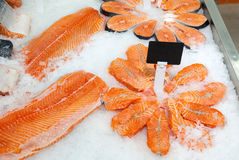 Slices of fresh raw salmon in ice ready to sale. At the market Royalty Free Stock Images