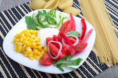 Slices of fresh raw vegetables with pasta and spaghetti Stock Images