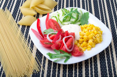 Slices of fresh raw vegetables on a white plate Stock Photo