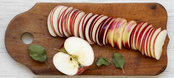Slices of fresh red apples on a rustic wooden board on a white wooden surface, top view. Flat lay, overhead, from above. Close-up.  stock photography