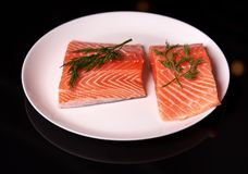 Slices of fresh salmon fillet on a white plate on a dark background with sprigs of dill stock photo