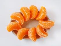 Slices of fresh tangerine. Plate of fresh tangerine slices on white background Royalty Free Stock Photo