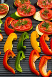Slices of fresh vegetables on a grill pan surface. Selective foc Stock Image