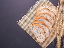 Slices of white bread with sesame seeds on black stone table bac. Slices of fresh white bread with sesame seeds on black stone table background. Top view and Royalty Free Stock Photo