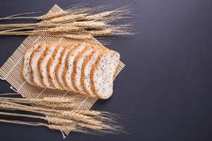 Slices of white bread with sesame seeds on black stone table bac. Slices of fresh white bread with sesame seeds on black stone table background. Top view and Royalty Free Stock Images