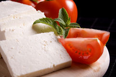 Slices of fresh white cheese. With tomato and mint leaves Stock Photo