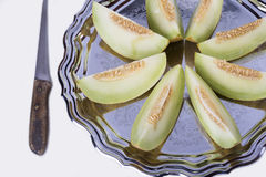 Slices of fresh yellow melon or cantaloupe  on the old tray with Stock Photo