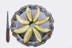 Slices of fresh yellow melon or cantaloupe  on the old tray with Royalty Free Stock Photos