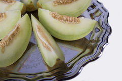 Slices of fresh yellow melon or cantaloupe  on the old tray  on Stock Photography