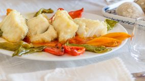 Portion slices of fried cod with slices of sweet bell pepper on the white dish, prepared for eating. Meditarranean healthy food