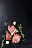 Slices of frozen meat with rosemare and onion on black paper stock images