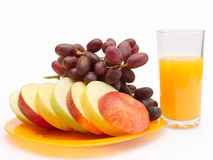 Slices of fruit and juice. Slices of apples, grapes on a plate and juice Royalty Free Stock Photography