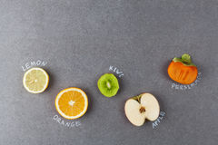 Slices of fruit with labels on stone Royalty Free Stock Photography