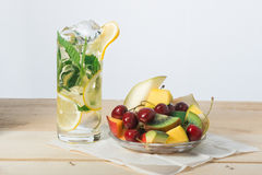 Slices of fruit, sweet cherry and lemon drink with ice in a glass on  surface from wooden boards Stock Photography