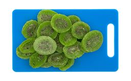 Slices of glazed kiwi fruit on a blue cutting board Royalty Free Stock Images