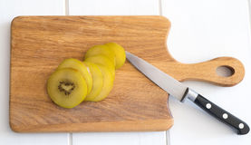 Slices of gold kiwi fruit on a chopping board with knife Royalty Free Stock Photography