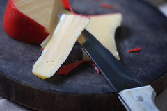 Slices of Gouda cheese on cutting board Stock Photos
