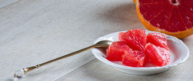 Slices of grapefruit on a plate, a spoon and a grapefruit Stock Images